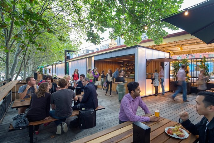People dining at Arbory Bar and Eatery, next to Flinders Street Station, beside the Yarra River.