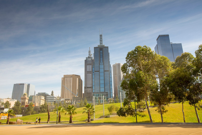 Trees, grass and city buildings at at Birrarung Marr park.