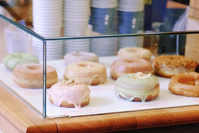 Iced doughnuts in a glass display cabinet.