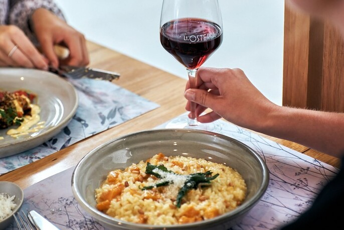 Hand holding a glass of red wine next to a bowl of risotto on a wooden table.
