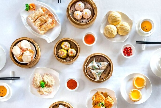 Assortment of dishes on a white table, including dumplings, buns and rolls.