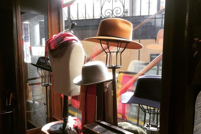 Hats for sale in a shop window.