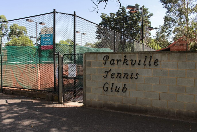 Exterior of Parkville Tennis Club showing wall, signage, gate, a fenced tennis court and trees in the background.