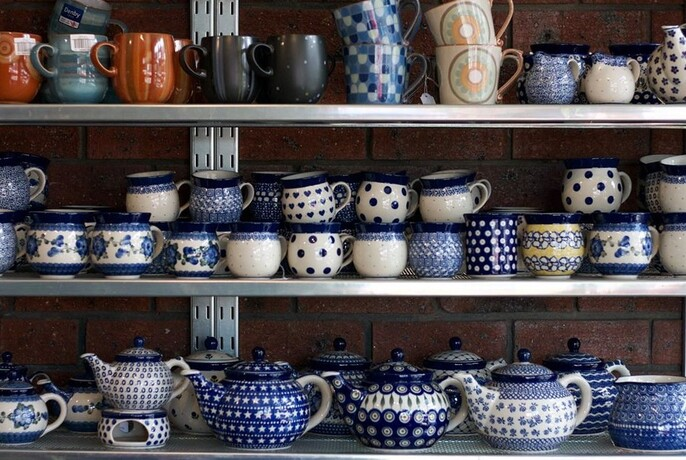 Display of blue and white ceramic teapots and mugs.